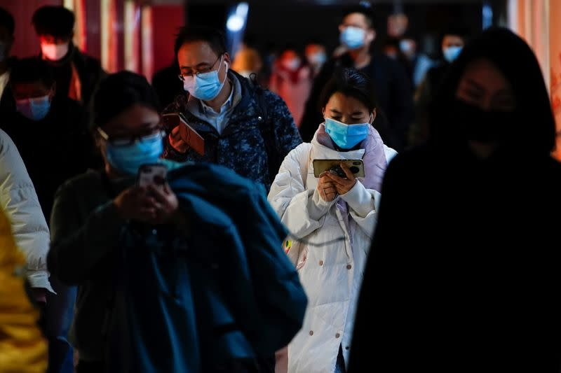 People wearing face masks use their cellphones at a subway station following the coronavirus disease (COVID-19) outbreak, in Shanghai