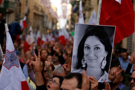 FILE PHOTO: A demonstrator carries a photo of murdered Maltese anti-corruption journalist Daphne Caruana Galizia in a protest in Valletta, Malta