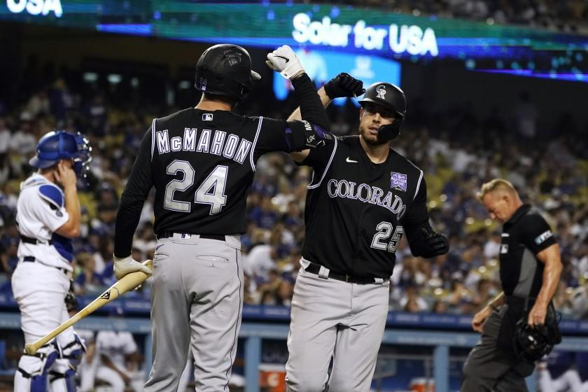The Rockies' C.J. Cron, right, celebrates his go-ahead solo homer with Ryan McMahon during the sixth inning Aug. 27, 2021.