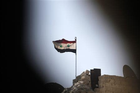 A Syrian national flag flutters over a building controlled by forces loyal to President Bashar Al-Assad in Ashrafieh, Aleppo