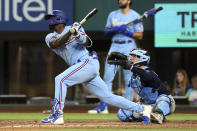 Texas Rangers Adolis Garcia, left, follows through on a solo home run in the sixth inning against the Minnesota Twins in a baseball game Sunday, June 20, 2021, in Arlington, Texas. (AP Photo/Richard W. Rodriguez)