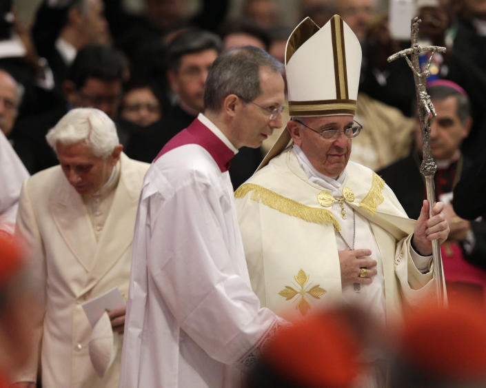 Pope Francis holds his pastoral staff after greeting Pope Emeritus Benedict XVI, left, ahead of a consistory inside the St. Peter's Basilica at the Vatican, Saturday, Feb.22, 2014. Benedict XVI has joined Pope Francis in a ceremony creating the cardinals who will elect their successor in an unprecedented blending of papacies past, present and future. (AP Photo/Alessandra Tarantino)