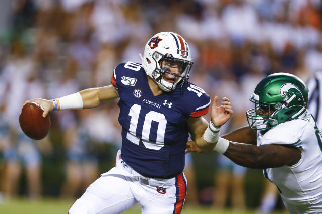 Auburn quarterback Bo Nix (10) scrambles away from Tulane defensive end Davon Wright (90) during the first quarter of an NCAA college football game Saturday, Sept. 7, 2019, in Auburn, Ala. (AP Photo/Butch Dill)