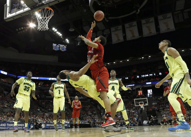 Baylor's Rico Gathers (2) falls backwards as Nebraska's Shavon Shields (31) makes contact while shooting during the first half of a second-round game in the NCAA college basketball tournament Friday, March 21, 2014, in San Antonio. Gathers was called for a foul on the play. (AP Photo/David J. Phillip)