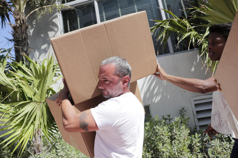 David Stein, an employee of the SLS Hotel, left, carries boxes of supplies from the hotel, Thursday, March 26, 2020, in Miami Beach, Fla. The sbe hotel chain is providing care packages to their employees now facing unemployment due to the new coronavirus pandemic. A record-high number of people applied for unemployment benefits last week as layoffs engulfed the United States in the face of a near-total economic shutdown caused by the coronavirus. (AP Photo/Lynne Sladky)