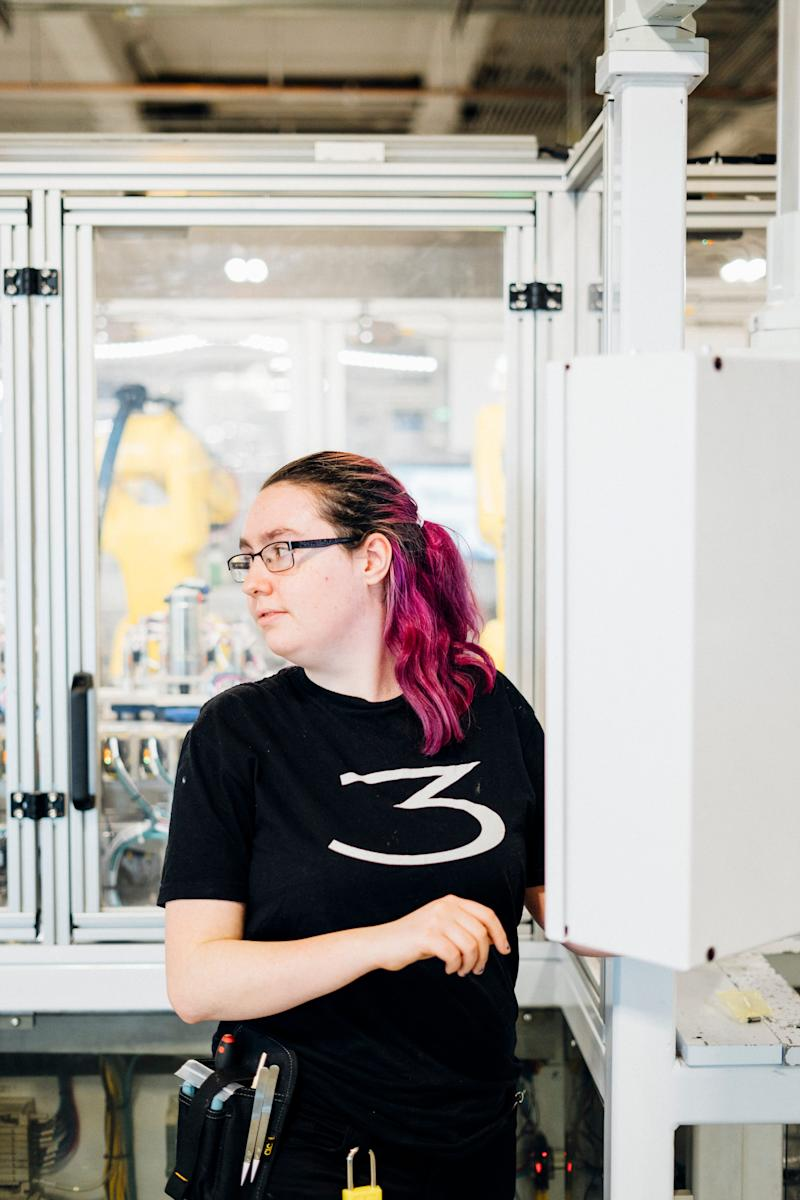 Isabelle West was hired at Tesla thanks to a program at her high school but struggled to find housing in the area. Here she stands at her work station inside the Tesla Gigafactory.