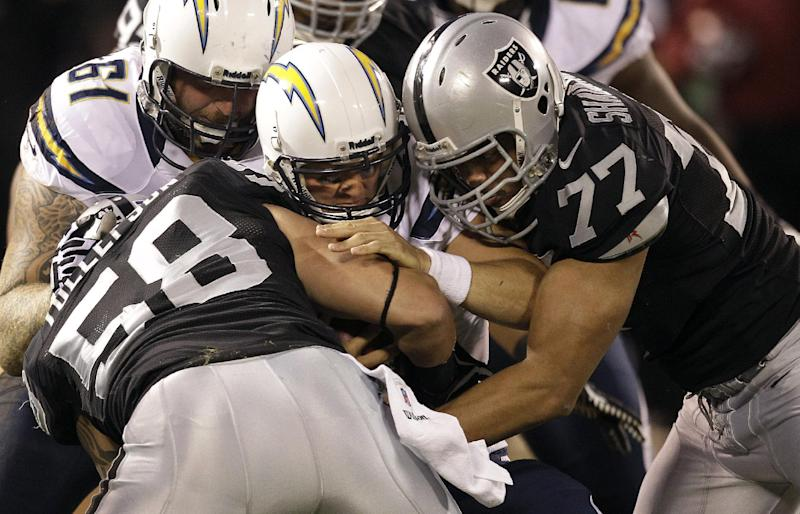 San Diego Chargers quarterback Philip Rivers is sacked by Oakland Raiders defensive end Dave Tollefson (58) and defensive end Matt Shaughnessy (77) during the first quarter of an NFL football game in Oakland, Calif., Monday, Sept. 10, 2012. (AP Photo/Ben Margot)