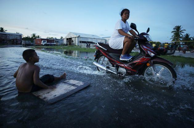 A woman rides her scooter through floodwaters occurring around high tide in a low-lying area near the airport in 2019 in Funafuti, Tuvalu. The South Pacific island nationof about 11,000 people has been classified as