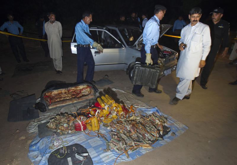 Pakistani police officers and explosive experts remove explosives and detonators from a car parked near the house of Pakistan's former President military ruler Pervez Musharraf, in Islamabad, Pakistan on Tuesday, April 23, 2013. Islamabad police chief Bani Amin says the explosive-laden vehicle was found parked about 150 metres (500 feet) from the main gate of Musharraf's house on the capital's outskirts Tuesday. (AP Photo/B.K. Bangash)