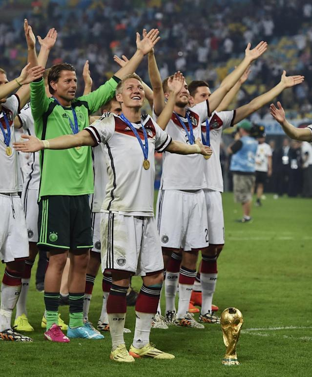 Germany's Bastian Schweinsteiger stands with the trophy after the World Cup final soccer match between Germany and Argentina at the Maracana Stadium in Rio de Janeiro, Brazil, Sunday, July 13, 2014. Germany won the match 1-0. (AP Photo/Martin Meissner)