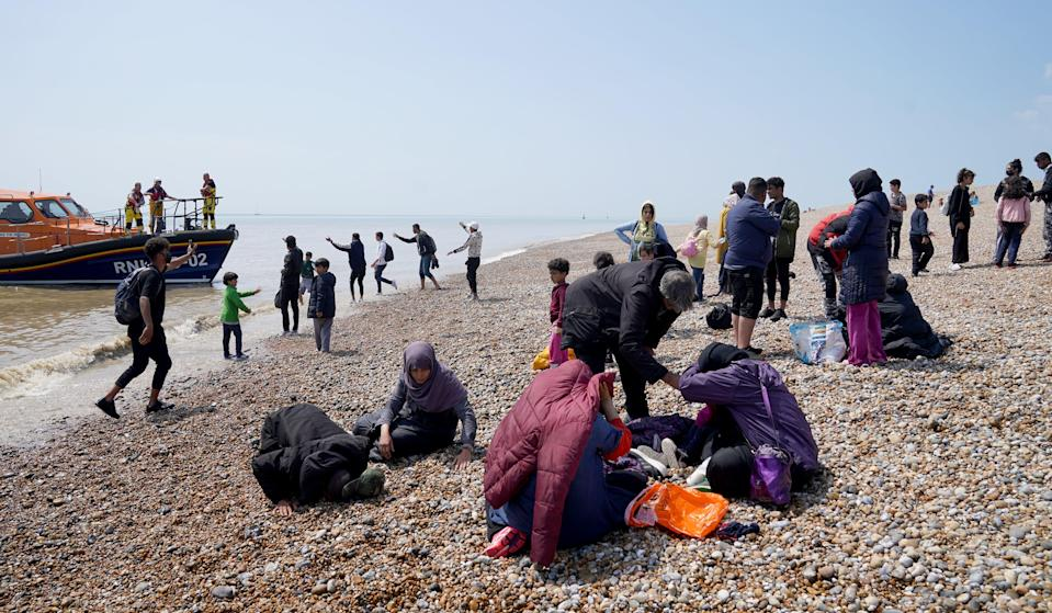People thought to be migrants make their way up the beach (Gareth Fuller/PA) (PA Wire)