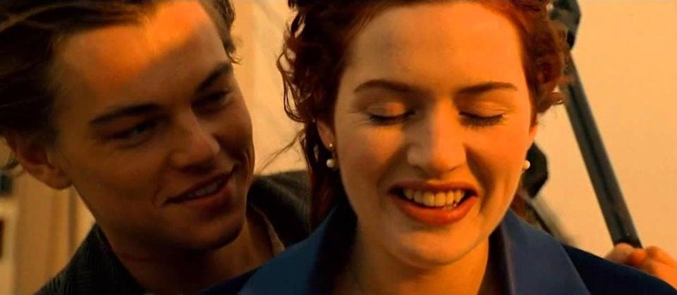 DiCaprio and Winslet stand at the front of the boat, smiling