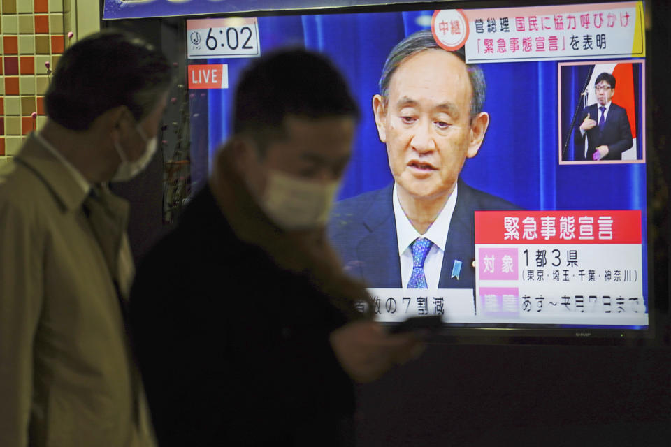 Pedestrians walk past a public TV with a live broadcast of a news conference by Japanese Prime Minister Yoshihide Suga after he declared a state of emergency Thursday, Jan. 7, 2021 in Tokyo. Suga declared a state of emergency Thursday for Tokyo and three other prefectures to ramp up defenses against the spread of the coronavirus. (AP Photo/Eugene Hoshiko)