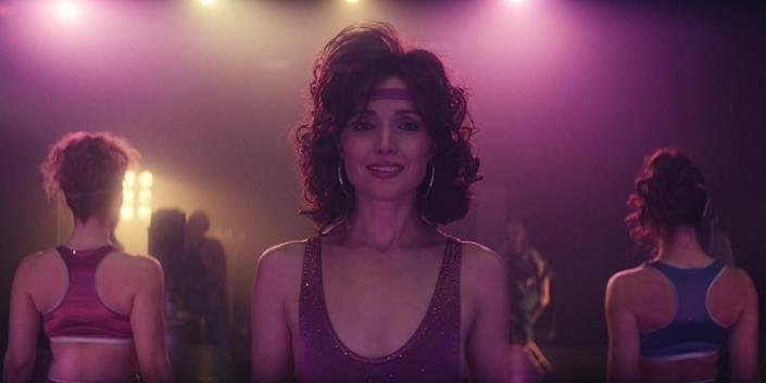 Rose Byrne in a leotard, narrow headband, large hoop earrings and a perm.