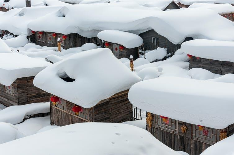 Small wooden buildings topped with thick snow.