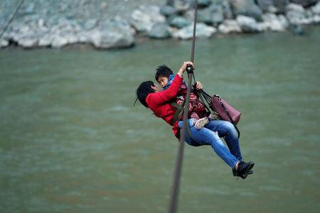Cha Huilan, a 40-year old Lisu woman, and her daughter leave Lazimi village with a zipline across the Nu River in Nujiang Lisu Autonomous Prefecture in Yunnan province, China, March 24, 2018. Picture taken March 24, 2018. REUTERS/Aly Song     TPX IMAGES OF THE DAY