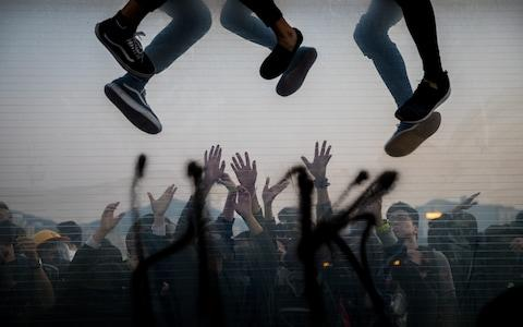 Protesters climbing over a highway dividers fleeing from police arrests as their comrades help on the other side during a demonstration - Credit: PA