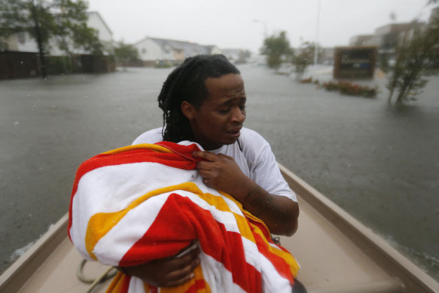 <p>Demetres Fair holds a towel over his daughter Damouri Fair, 2, as they are rescued by boat by members of the Louisiana Department of Wildlife and Fisheries and the Houston Fire Department during flooding from Tropical Storm Harvey in Houston, Monday, Aug. 28, 2017. (Photo: Gerald Herbert/AP) </p>