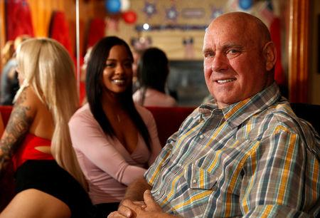 FILE PHOTO: Dennis Hof, owner of the Moonlite BunnyRanch legal brothel and recent winner of the Republican primary election for Nevada State Assembly District 36, sits in the parlor of the brothel with legal prostitutes Chantel Baby (L) and Maggie Monroe, in Mound House, Nevada, U.S. June 16, 2018.    REUTERS/Steve Marcus/File Photo