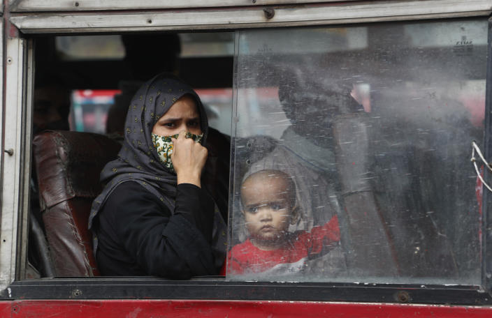 A woman and child look out the window of a a bus as they leave for their village following a six-day lockdown put into place to control the rising cases of coronavirus infections, in New Delhi, India, Tuesday, April 20, 2021. India recorded over 250,000 new infections and over 1,700 deaths in the past 24 hours alone, and the U.K. announced a travel ban on most visitors from the country this week. (AP Photo/Manish Swarup)