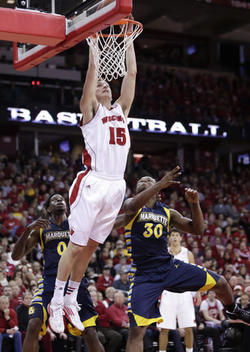 Wisconsin's Sam Dekker (15) dunks over Marquette's Jamil Wilson, left, and Deonte Burton during the second half of an NCAA college basketball game Saturday, Dec. 7, 2013, in Madison, Wis. Dekker had a team high 20 points and 10 rebounds in Wisconsin's 70-64 win. (AP Photo/Andy Manis)