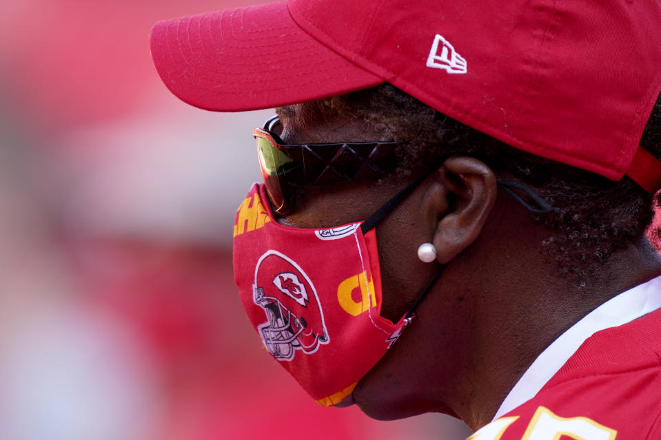 A fan wears a face masks as she watches the Kansas City Chiefs during an NFL football training camp Saturday, Aug. 22, 2020, at Arrowhead Stadium in Kansas City, Mo. The Chiefs opened the stadium to 2,000 season ticket holders to watch practice as the team plans to open the regular season with a reduced capacity of approximately 22 percent or normal. (AP Photo/Charlie Riedel)