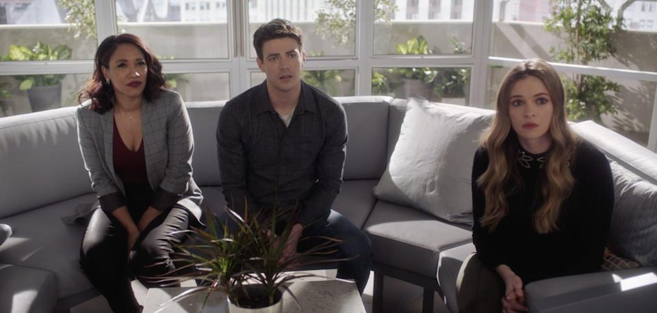 """Candice Patton, Grant Gustin, and Danielle Panabaker sitting on a couch on season seven of """"The Flash."""""""
