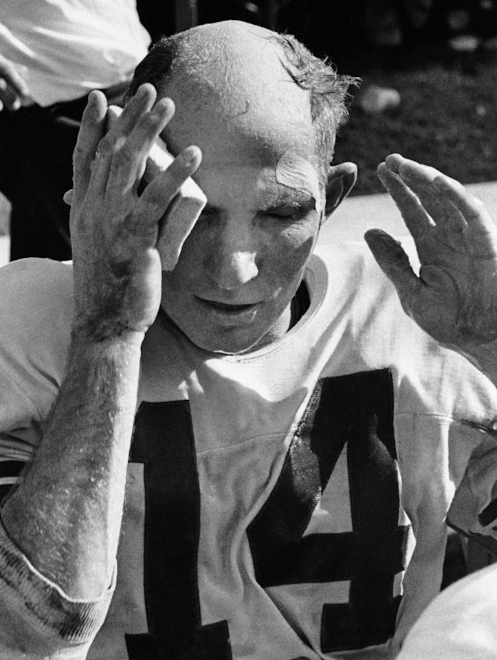 FILE - In this Oct. 7, 1962, file photo, New York Giants quarterback Y.A. Tittle wipes his face after running for a touchdown against the St. Louis Cardinals, in St. Louis. Tittle, the Hall of Fame quarterback and 1963 NFL Most Valuable Player, has died. He was 90. His family confirmed to LSU, where Tittle starred in college, that he passed away. No details were immediately provided. (AP Photo/File)
