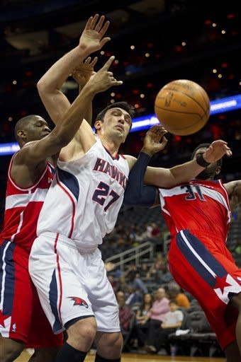 Atlanta Hawks' Zaza Pachulia (27) loses the ball against Washington Wizards' Kevin Seraphin (13) and Chris Singleton (31) during the first half of an NBA basketball game in Atlanta, Friday, March 16, 2012. (AP Photo/Rich Addicks)