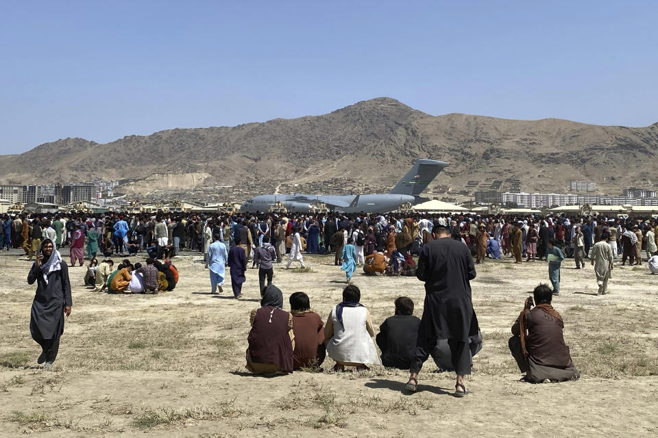 FILE - In this Aug. 16, 2021, file photo, hundreds of people gather near a U.S. Air Force C-17 transport plane at the perimeter of the international airport in Kabul, Afghanistan. A school district in a San Diego suburb that is home to a large refugee population says many of its families who had taken summer trips to Afghanistan to see their relatives have gotten stuck there with the chaos following the withdrawal of U.S. troops. (AP Photo/Shekib Rahmani)