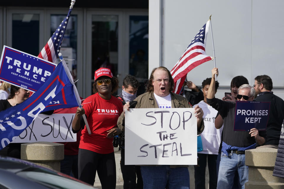 """Protesters hold signs that read """"Stop the steal,"""" """"Promises kept"""" and """"Trump Pence"""""""