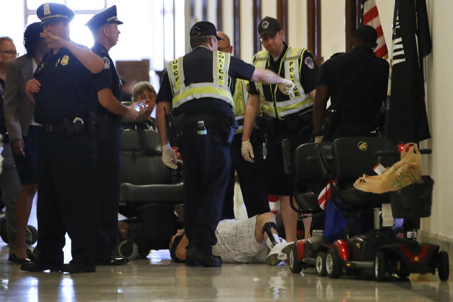 <p>Capitol Police prepare to remove a man from a sit-in of Senate Majority Leader Mitch McConnell's office, as he and others protest proposed caps to Medicaid Thursday, June 22, 2017, on Capitol Hill in Washington. (Photo: Jacquelyn Martin/AP) </p>