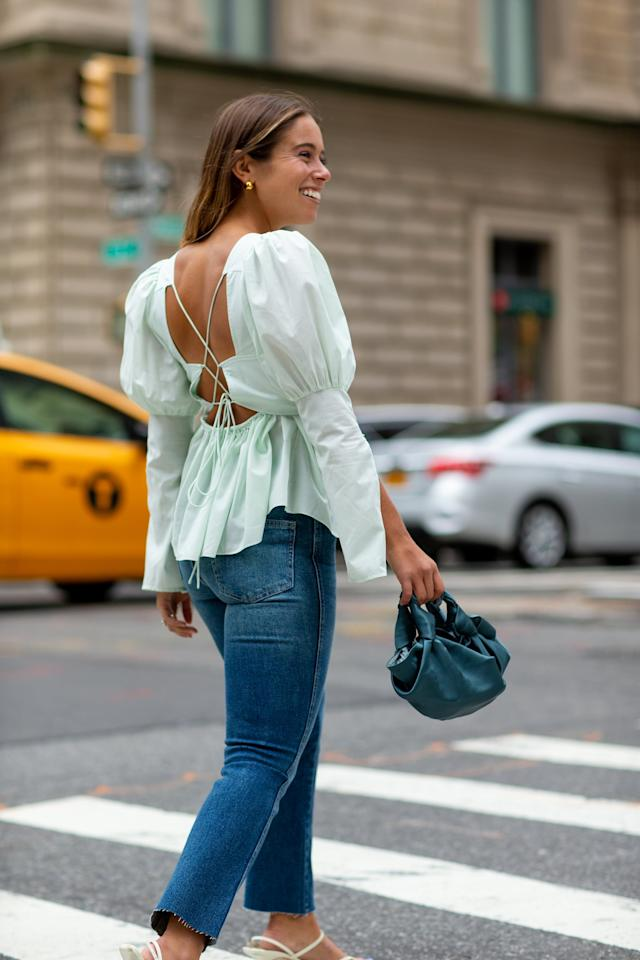 <p>Give your jeans a dressed-up feel by styling with a puffy-sleeve top, a silky bag, and strappy sandals. Bonus points for a top that has pretty back detailing like this Allina Liu style.   </p>