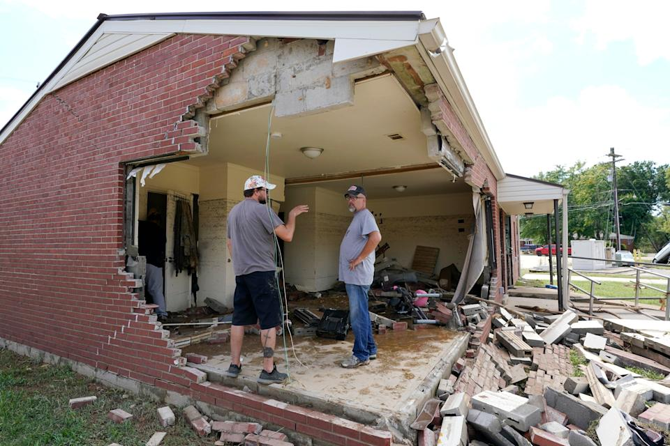 Brian Mitchell, right, looks through the damaged home of his mother-in-law along with family friend Chris Hoover in Waverly on Sunday (Mark Humphrey/AP)