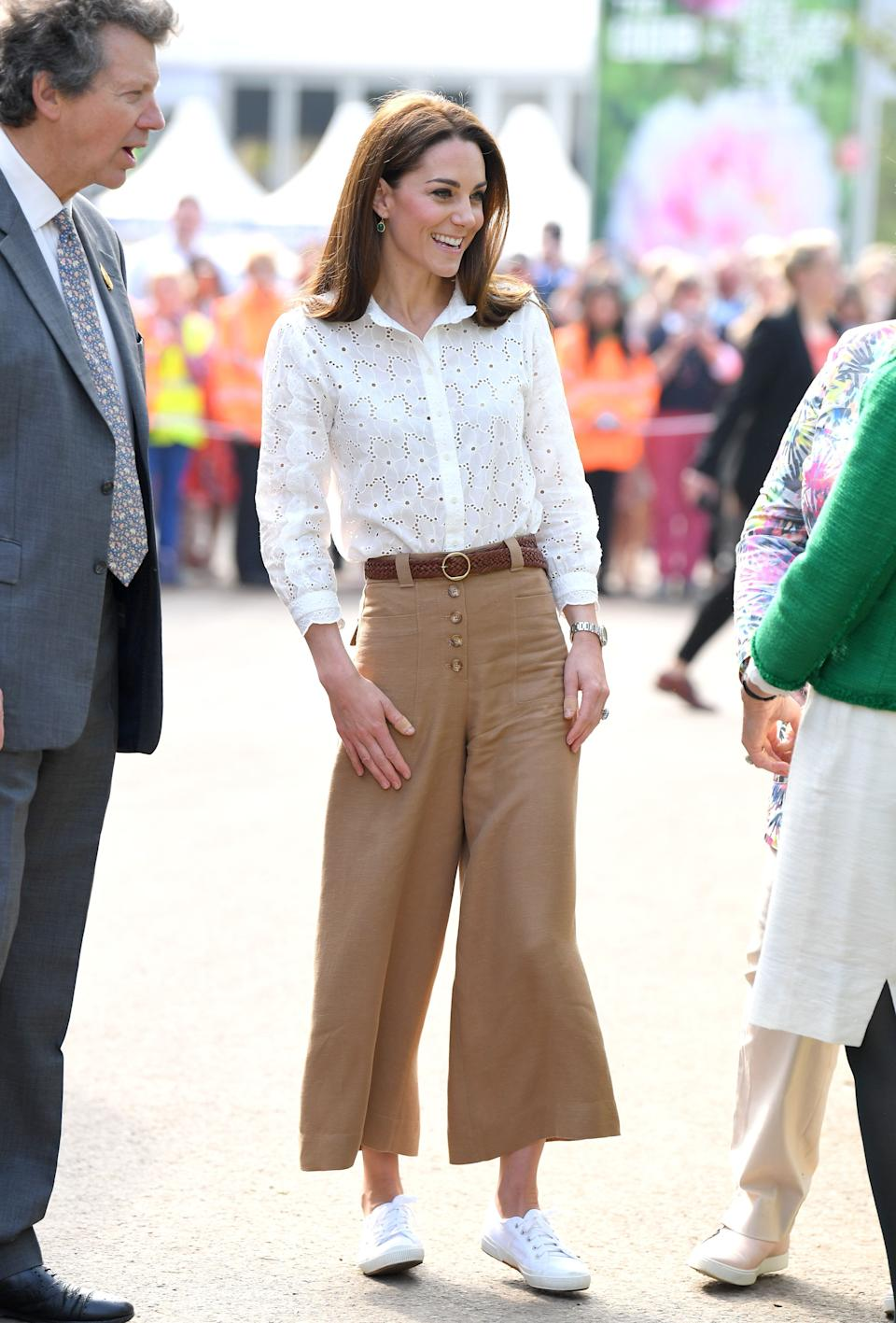 The Duchess of Cambridge sports cropped pants and a lightweight blouse with her Superga sneakers earlier this summer. (Photo: Getty Images)