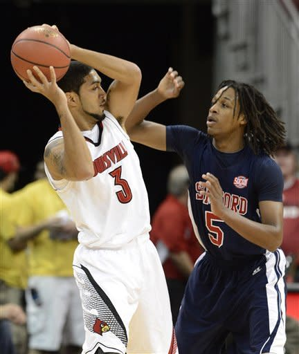 Louisville's Peyton Siva, left, tries to keep the ball away from the defensive pressure of Samford's Russell Wilson during the first half of an NCAA college basketball game Thursday, Nov. 15, 2012, in Louisville, Ky. (AP Photo/Timothy D. Easley)