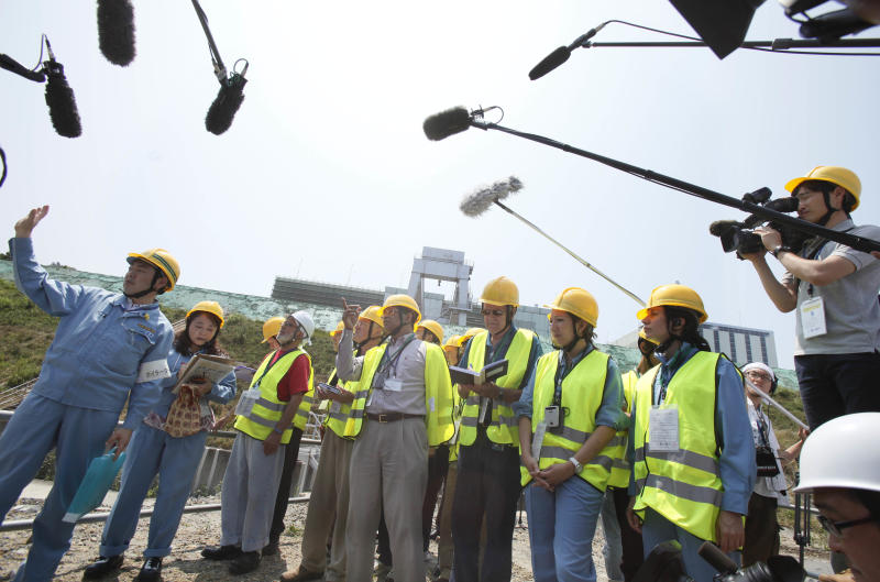 Media microphones surround International Atomic Energy Agency group head Sujit Samaddar, center, and other experts in yellow vests, during their inspection of the Onagawa nuclear power plant in Onagawa, Miyagi prefecture, northeastern Japan, Tuesday, July 31, 2012. The 20-member IAEA mission, first at the Onagawa plant, about 120 kilometers (74 miles) north of Fukushima Dai-ichi nuclear plant, since the crisis, aims to find out the extent of damage at the plant from the magnitude 9.0 quake. (AP Photo/Koji Sasahara)