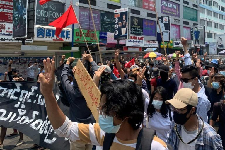 Protesters hold up the three finger salute as they take part in a demonstration against the military coup in Tarmwe township in Yangon on April 26, 2021