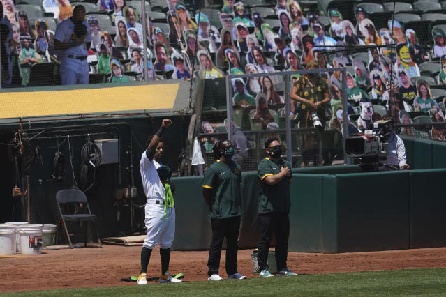Oakland Athletics' Khris Davis raises his fist during the national anthem before a baseball game between the Athletics and the Los Angeles Angels in Oakland, Calif., Saturday, July 25, 2020. (AP Photo/Jeff Chiu)