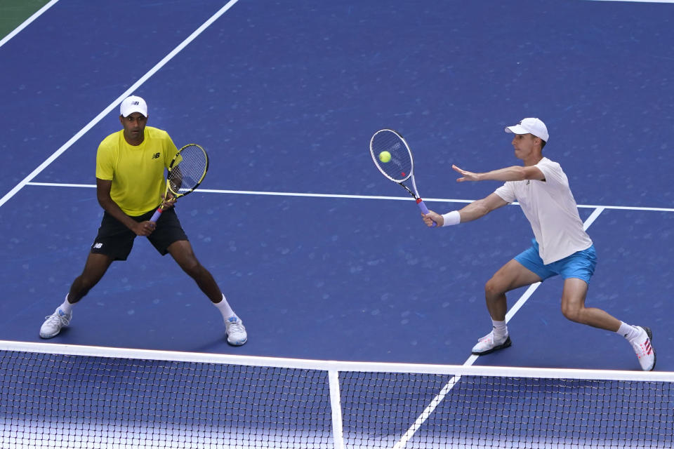 Joe Salisbury, of Great Britain, returns the ball as teammate Rajeev Ram, of the United States, watches during their men's doubles final match against Bruno Soares, of Brazil, and Jamie Murray, of Great Britain, at the US Open tennis championships, Friday, Sept. 10, 2021, in New York. (AP Photo/Elise Amendola)