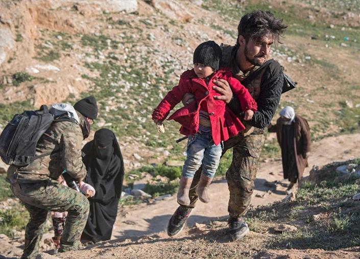 A fighter with the US-backed Syrian Democratic Forces helps women and children who fled the Islamic State group's last pocket of territory in eastern Syria on February 12, 2019 (AFP Photo/Fadel SENNA)