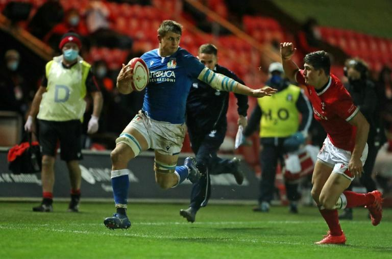 Try-scorer -- Italy flanker Johan Meyer (C) runs past Wales wing Louis Reed-Zammit (R) on his way to the line
