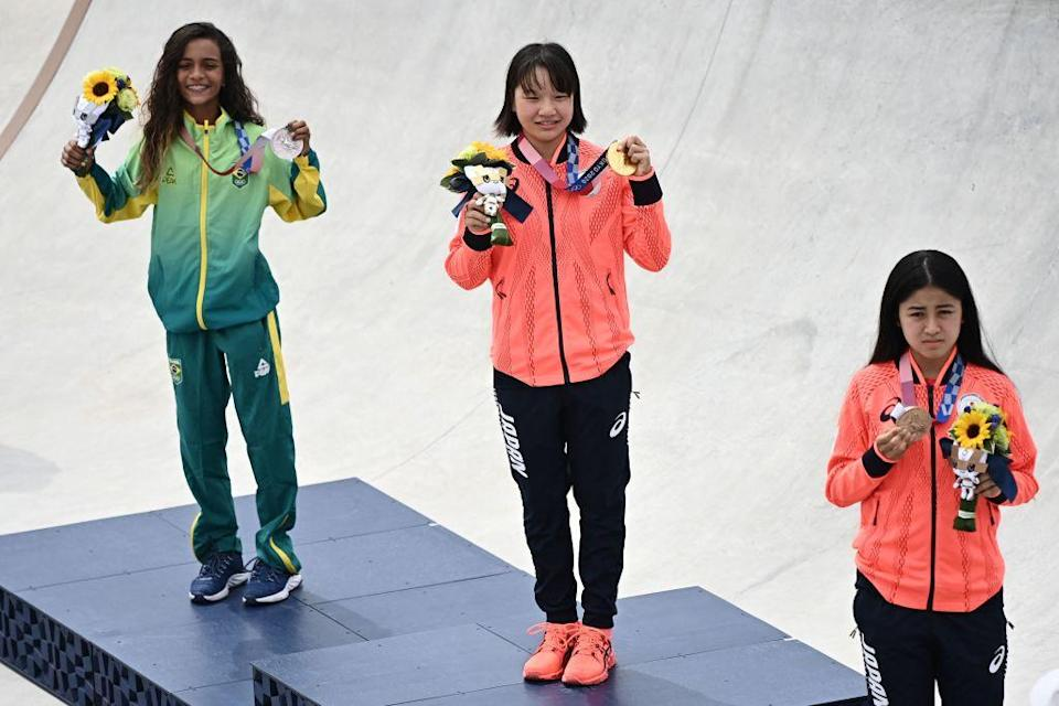 """(Left to right) Brazil's Rayssa Leal (silver), Japan's Momiji Nishiya (gold) and Japan's Funa Nakayama (bronze) pose during the medal ceremony of the podium ceremony of the skateboarding women's street final of the Tokyo 2020 Olympic Games at Ariake Sports Park in Tokyo on July 26, 2021.<span class=""""copyright"""">Lionel Bonaventure—AFP/Getty Images</span>"""