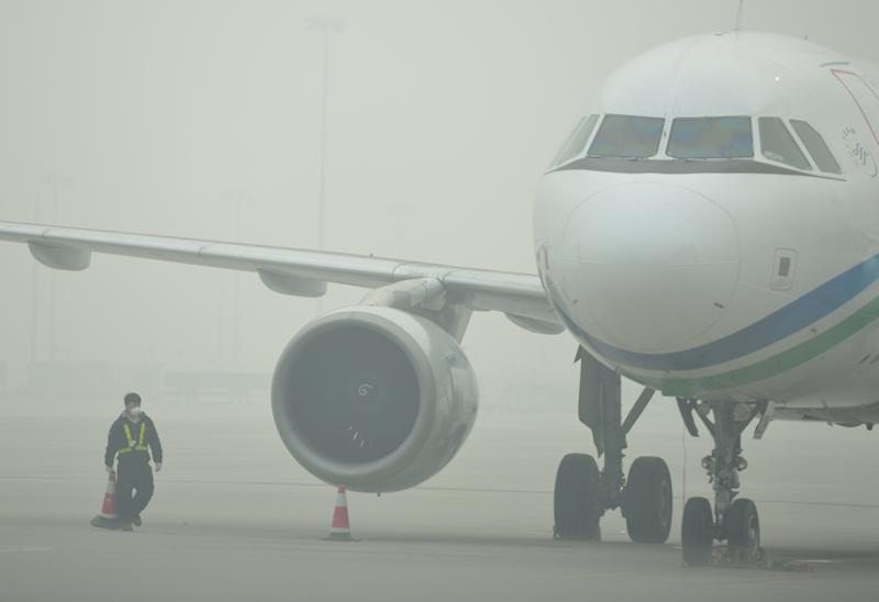 An airport ground crew worker wears a mask in thick smog on the tarmac of Hongqiao airport in Shanghai as severe pollution blankets the city on December 6, 2013. The cities most harmful PM2.5 density soared to 468 micrograms per cubic metre by midnight more than 10 times the level deemed safe by the World Health Organization state media said. AFP PHOTO/Peter PARKS (Photo credit should read PETER PARKS/AFP/Getty Images)