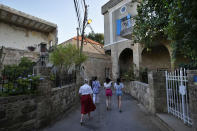Tourists visit Batroun village, north of Beirut, Lebanon, Friday, July 2, 2021. With their dollars trapped in the bank, a lack of functioning credit cards and travel restrictions imposed because of the pandemic, many Lebanese who traditionally vacationed over the summer at regional hotspots are also now turning toward domestic tourism. (AP Photo/Hassan Ammar)