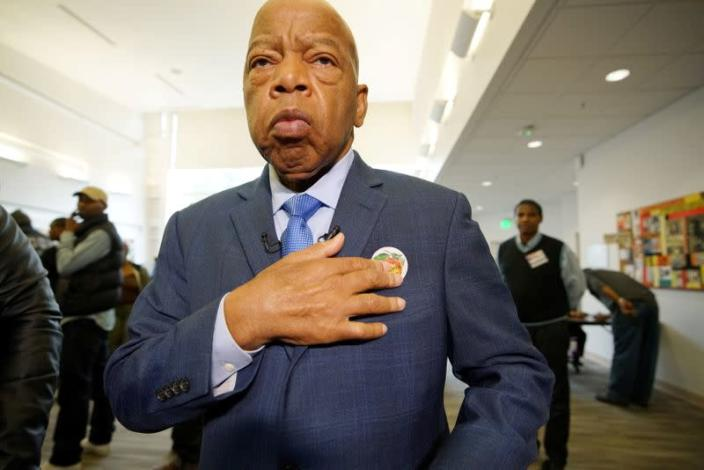 """FILE PHOTO: U.S. Democratic Representative John Lewis puts on his """"I'm Georgia Voter"""" sticker after casting a ballot in midterm election at Wolf Creek Library in Atlanta, Georgia"""
