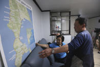 Shin Yun-sun, center, and Lee Gwang-nam, right, watch the map of Sakhalin during an interview at Shin's house in Seoul, South Korea Wednesday, July 29, 2020. The thousands of husbands and fathers who never returned from Sakhalin after eight decades is a largely forgotten legacy of Japan's brutal rule of the Korean Peninsula before the end of World War II. Shin, 75, and Lee, 76, are among about 400 aging relatives who hope to bring back the remains of the missing workers, seeking closure after years of emotional distress and economic hardship that affected many of the broken families.(AP Photo/Ahn Young-joon)