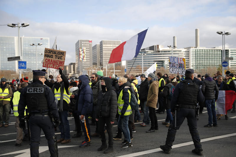 Yellow vests protesters holding a French flag march in Paris, Saturday, Dec. 7, 2019. A few thousand yellow vest protesters marched Saturday from the Finance Ministry building on the Seine River through southeast Paris, pushing their year-old demands for economic justice and adding the retirement reform to their list of grievances. (AP Photo/Francois Mori)