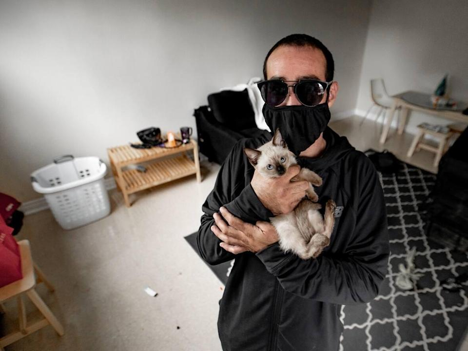 Chris, who was sleeping in a park until a few weeks ago, with his kitten in his new permanent housing space. (Craig Chivers / CBC - image credit)