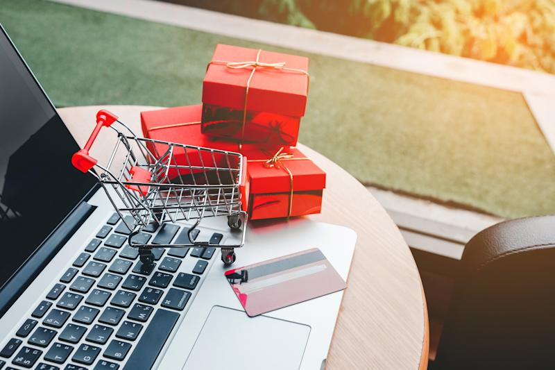 A miniature shopping cart, miniature boxes, and a credit card on a laptop.